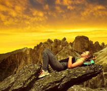 Tourist lying on a rock in Dolomites Stock Photos