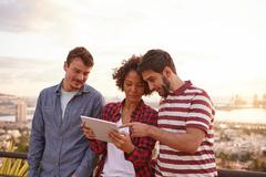 Three friends looking and pointing at a tablet looking at it with interest wh Stock Photos