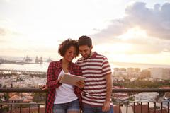 Happy young couple sharing jokes on the tablet with the sun setting behind th Stock Photos