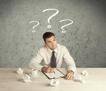 Businessman at desk with question mark Stock Photos