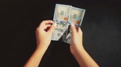 Woman hands count a pack of dollars on the black background Stock Footage