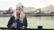 Young woman drinking coffee and talking on the mobile phone. Woman talking via Stock Footage