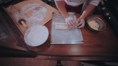 Baker rolls out the dough on a wooden kitchen table sprinkled with flour Stock Footage