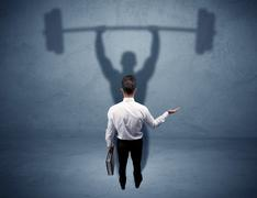 Businessman with weight lifting shadow Stock Photos