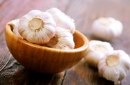 Fresh garlic in bowl on a table Stock Photos