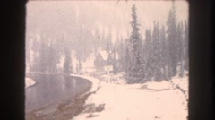 1962: a wet winding road with beautiful snow covered pine trees on either side Stock Footage