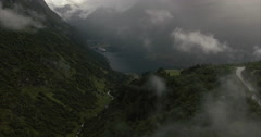 Over the clouds shot revealing fjord Stock Footage