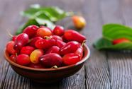 Cornelian cherry berry in bowl on wooden background Stock Photos