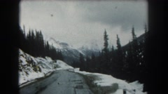 1962: an icy road with snow covered mountains on either side Stock Footage