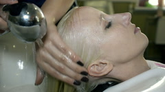 Close Up Stylist washing hair with shampoo young girl Stock Footage
