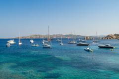 Luxury sailing and motor yachts at scenic Porto Massimo bay Stock Photos