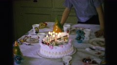 1964: child preparing to blow out candles on his birthday cake at a birthday Stock Footage