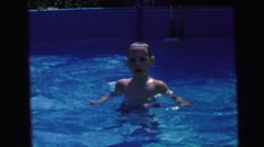 1964: kids playing in a backyard pool a boy dives underwater and then pops back Stock Footage