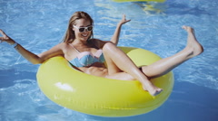 Young girl with sunglasses on the yellow rubber ring posing in the swimming pool Stock Footage