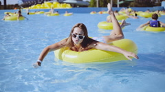 Girl with sunglasses on the yellow rubber ring swims in the swimming pool Stock Footage