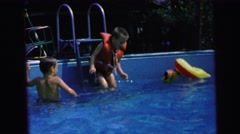 1964: young boy jumps into swimming pool with life jacket and makes a splash Stock Footage