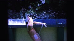 1964: someone jumping or diving into the water in an above ground pool CAMDEN Stock Footage