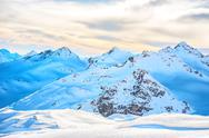 Snowy blue mountains in clouds Stock Photos