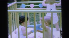 1964: three babies in a crib outdoors and two are playing with a toy  Stock Footage