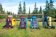 Four backpacks standing near fence Stock Photos