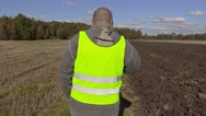 Farmer talking on the phone and go to the tractor Stock Footage
