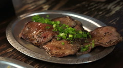 Japanese grill beef tongue slice on plate with lemon in Izakaya restaurant style Stock Footage