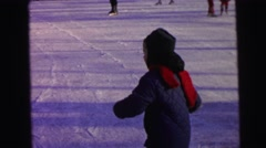 1964: a child with a red scarf ice-skating and then falling down on the ice Stock Footage