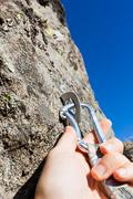 Security concept: climber inserts a quick-draw in anchor on rock wall outdoor Kuvituskuvat