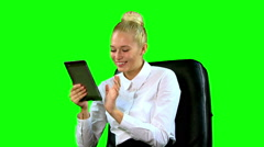Young Woman with Tablet in Chair Laughting. Green screen. Middle Stock Footage