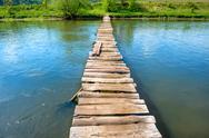 Old wooden bridge through the river Stock Photos