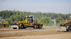 Grader road construction with a blade create a flat surface during the grading Stock Footage