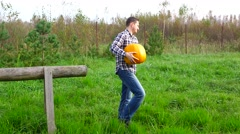 Handsome strong farmer take big pumpkin and go away Stock Footage