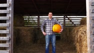 Pleased farmer stand in hayloft with orange pumpkin, pick up and go away Stock Footage