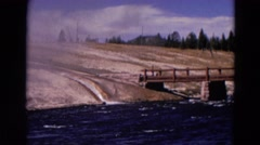 1967: water is falling over the rock to the blue water body with a bridge Stock Footage