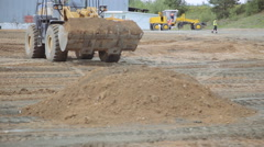 Front loader leveled and pour sand in construction site Stock Footage