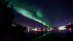 Aurora borealis Reykjavik city lights houses trees water reflection realistic 4k Stock Footage