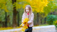Adorable little girl outdoors at beautiful autumn day playing with leaves Stock Footage
