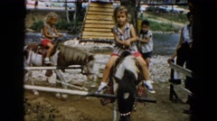 1961: little girls and little boys enjoying livestock, circular pony rides Stock Footage