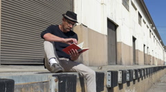 MAN READS A BOOK ON A LOADING DOCK. Stock Footage