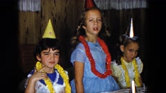 1961: little girls celebrating around table while wearing party hats and leis Stock Footage