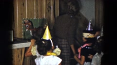 1961: several little girls wearing shiny birthday hats at a party indoors Stock Footage