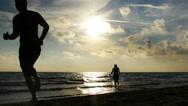 Couple having fun running on the beach Stock Footage