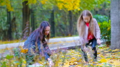 Adorable little girl and happy mother enjoy fall day in autumn park outdoors Stock Footage