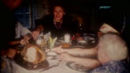 Family gathers at kitchen table for turkey dinner, 3677 vintage film home movie Stock Footage