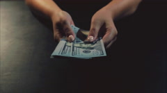 Woman hands showing a pack fan of dollar bills on the black background Stock Footage
