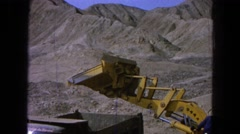 1965: an excavator throwing dirt in a truck is in a sand-filled and dry place. Stock Footage