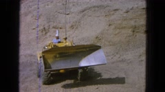 1965: bulldozer working on construction site moving earth to dump truck MEXICO Stock Footage