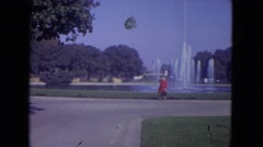 1972: a woman in a red jacket, standing in front of a large pond  Stock Footage