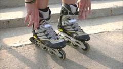 Man preparing for roller skating, putting on rollerskates Stock Footage