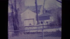 1972: someone walking toward the fence recording someone moving around  Stock Footage